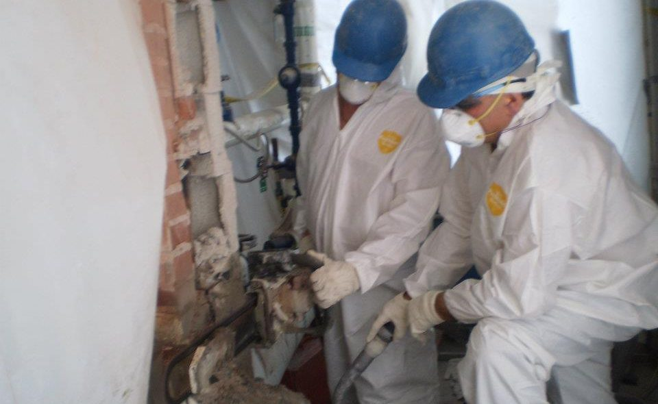 Workers cutting into concrete via EPA regulations