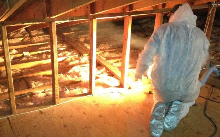 Worker in attic adding insulation